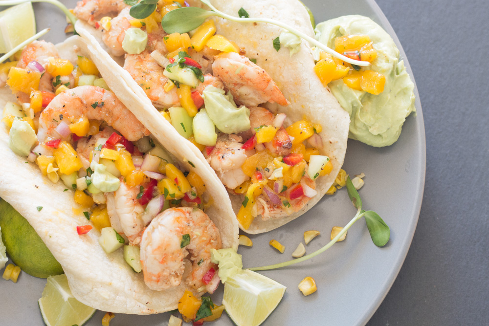 """Healthy shrimp tacos with cucumber mango salsa and avocado """"cream"""" sauce is a great summer weeknight meal or your next taco bar!"""